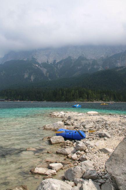 türkisblaues Wasser und wolkenverhangenes Zugspitzmassiv