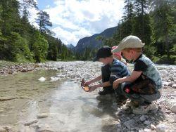 die Kinder sind am Wasser ins Spiel vertieft