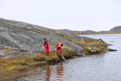 die Kinder vergnügen sich mit einem gefundenen Grönlandpaddel